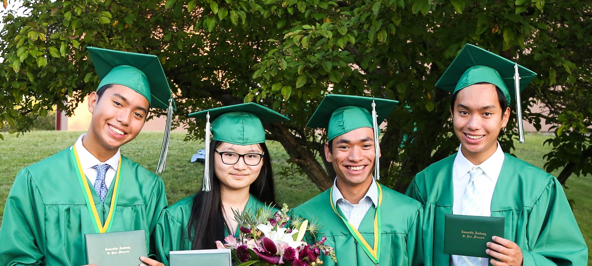 Four graduates in robes smile outdoors following graduation.